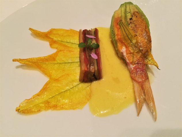 Rotbarbe gefüllt mit Artischockenkaviar und Kreuzkümmel in einer Zucchiniblüte, gelbe Paprikasauce mit Arganöl