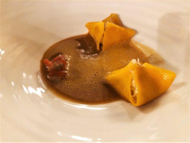 Dünner Kürbis-Raviolo gefüllt mit Taschenkrebsfleisch und Frischkäse auf Schalentier-Jus