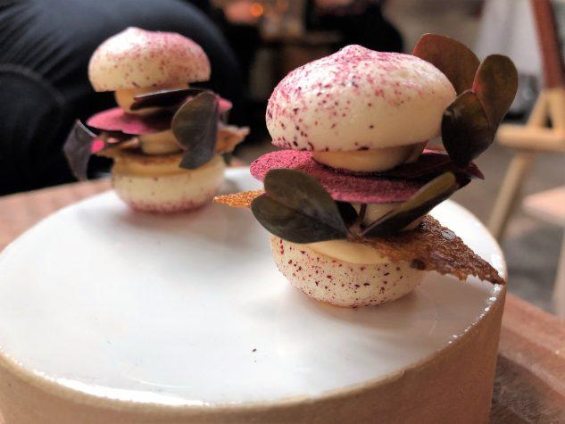 Apéro: Trauben-Macaron, geschlagene Foie Gras, konzentrierter Portwein, dänischer Roggen & Hibiskus