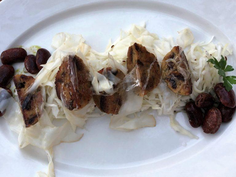 Marinierte Semmelknödelscheiben mit Weißkrautsalat, Speck und Käferbohnen