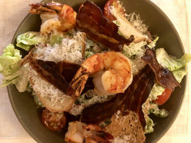 Caesar Salad mit krossem Speck, Sauerteigbrotchips und gehobeltem Parmesan mit gebratenen Garnelen